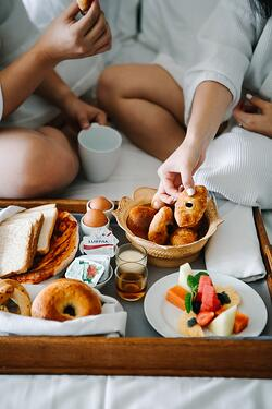 Couple eating room service breakfast on the hotel bed