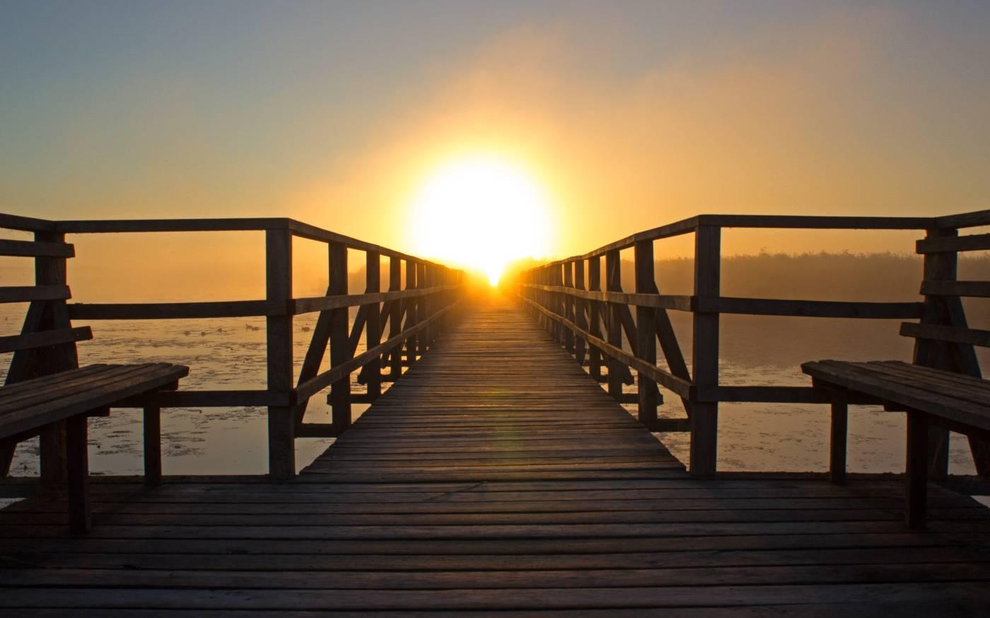 Eine Brücke mit der untergehenden Sonne am Horizont