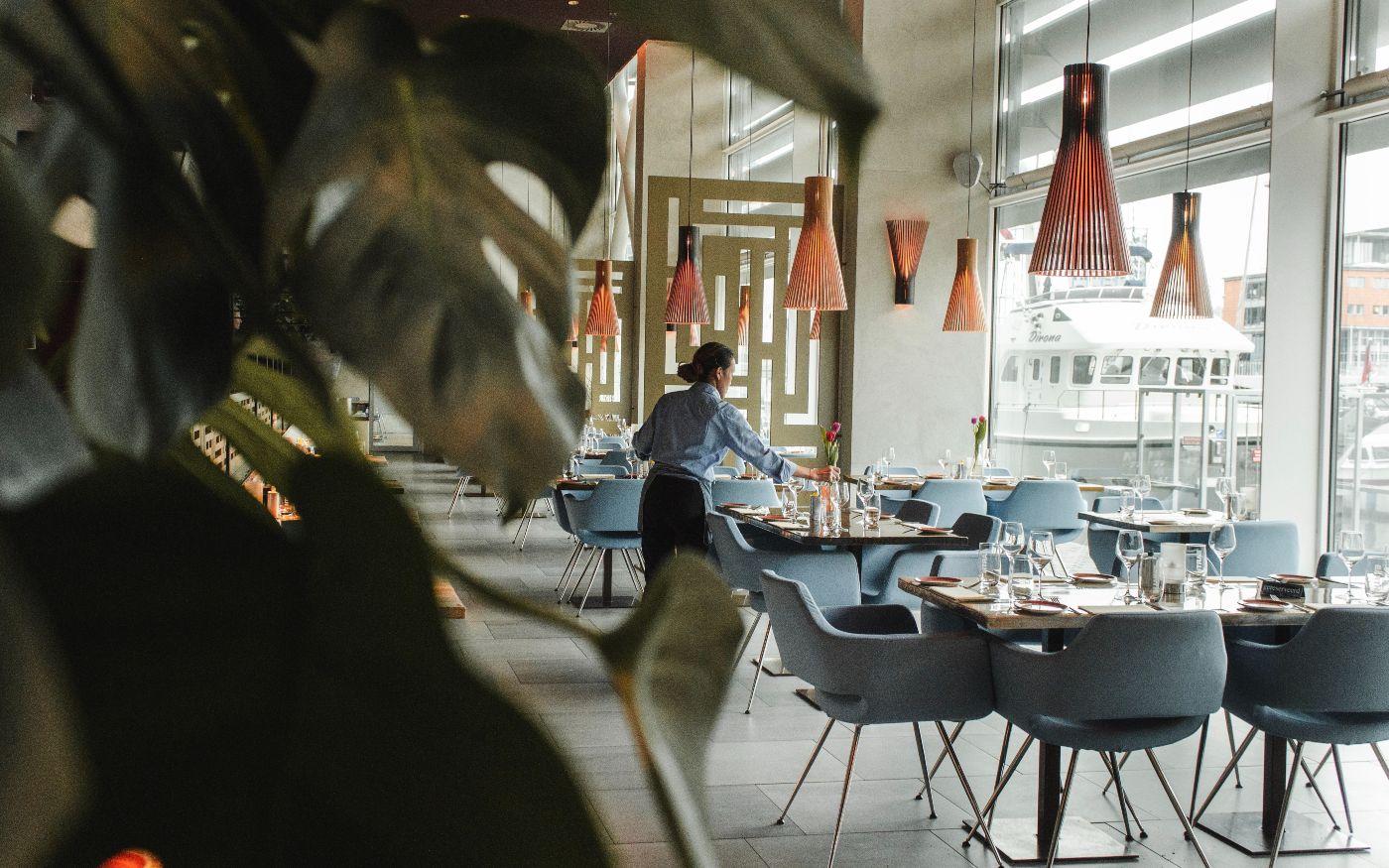 Eine Servicemitarbeiterin des Hotelrestaurants beim Eindecken der Tischen