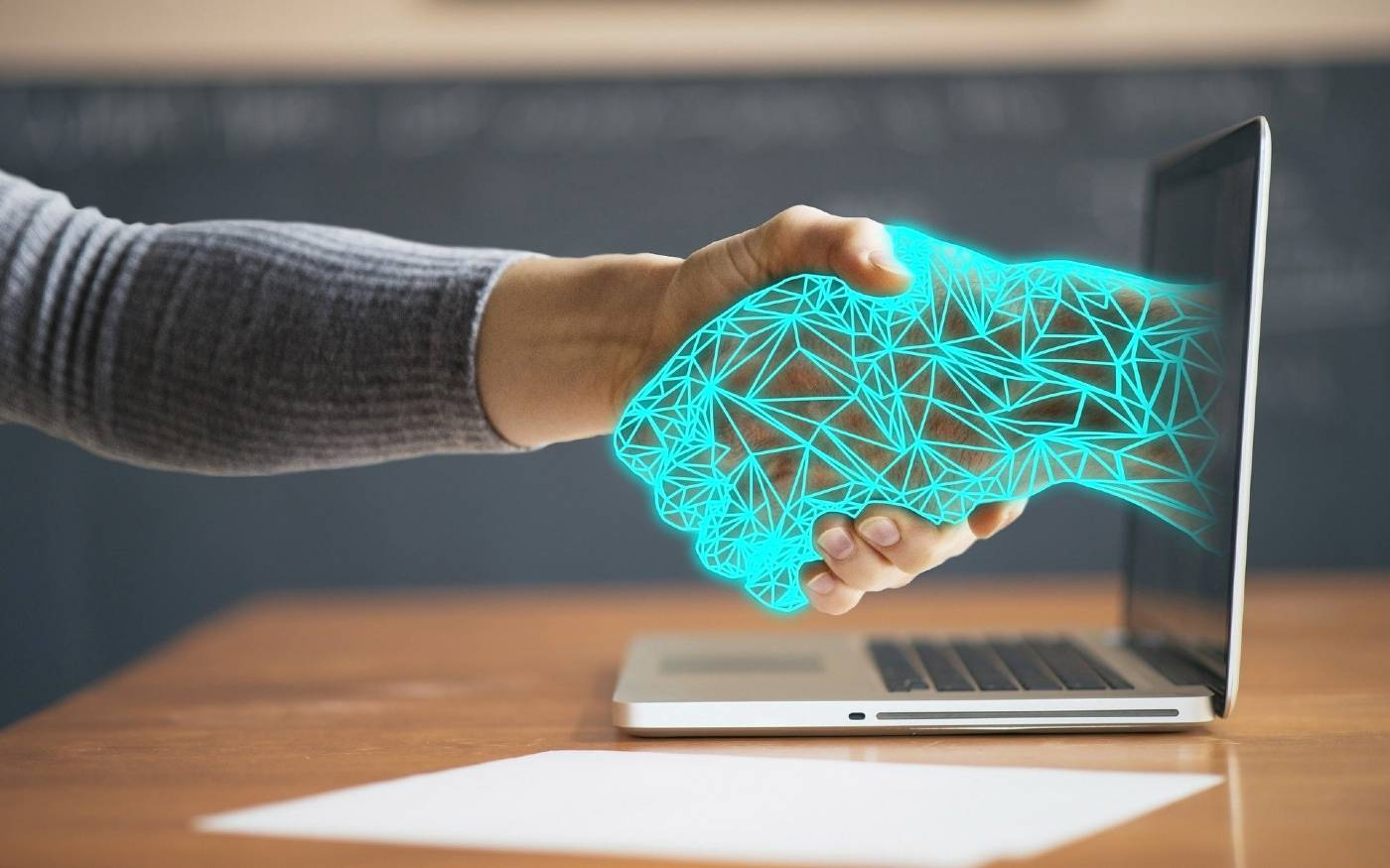 Human hand shaking an AI hand coming out of a laptop