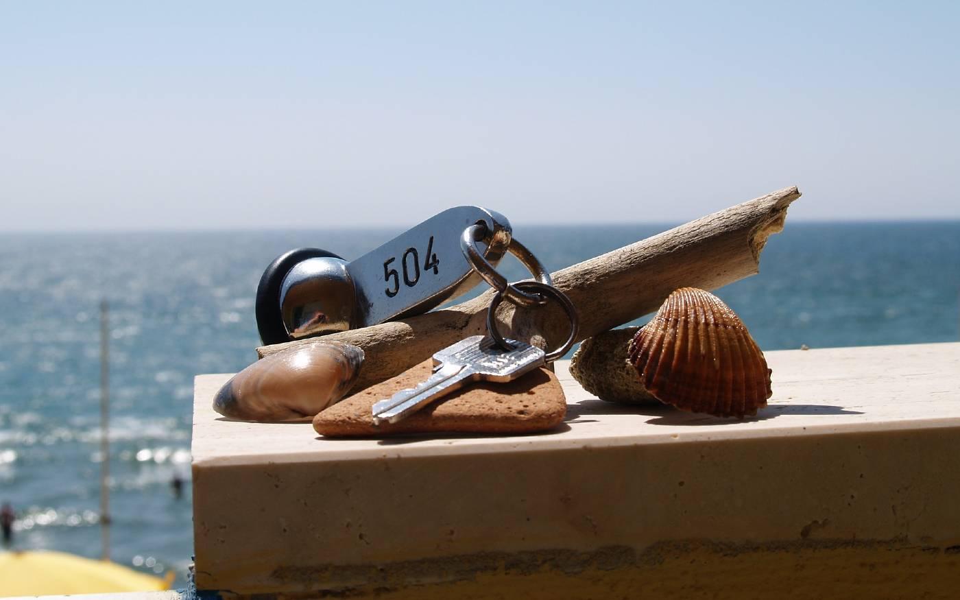 Hotelzimmerschlüssel mit Deko vor einem Strandhintergrund