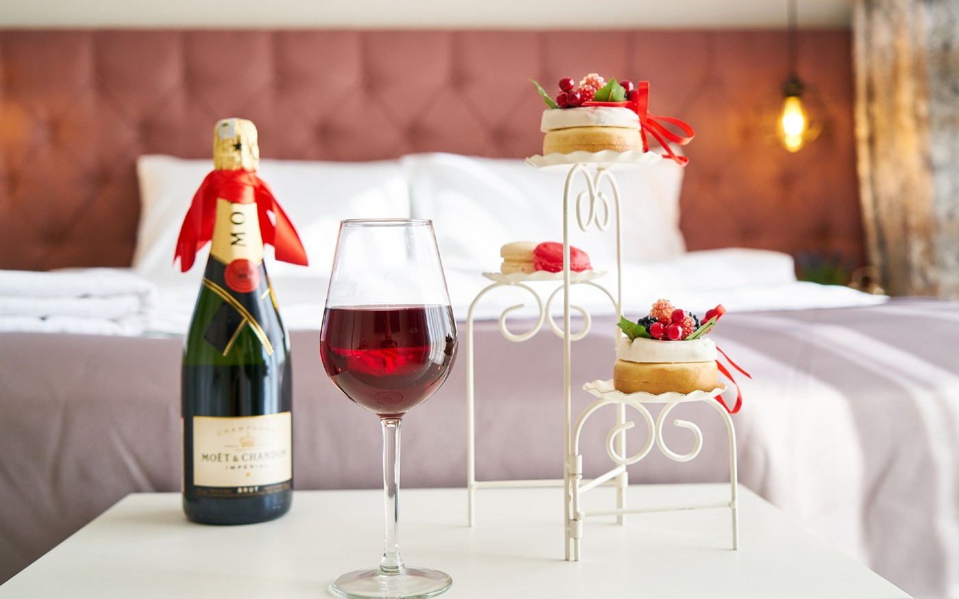 Bottle of champagne next to some cakes in a hotel room